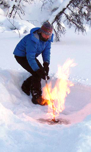 AF researcher Katey Walter lights a pocket of methane on a thermokarst lake in Siberia in March of 2007. Igniting the gas is a way to demonstrate, in the field, that it contains methane