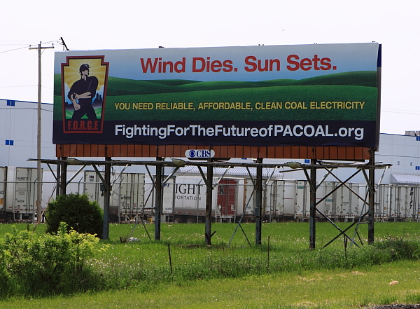 Attacking wind and solar while promoting coal (with truck depot along a highway as a backdrop).
