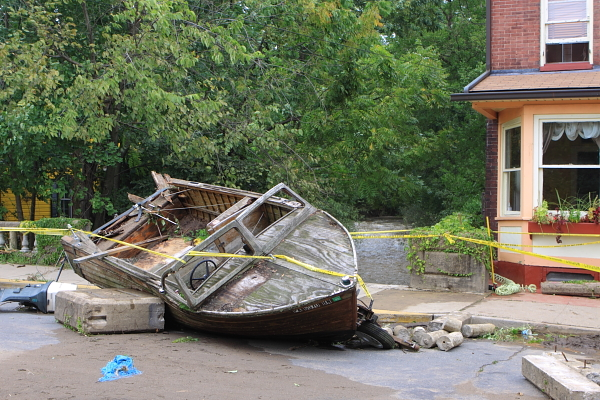 (South Union Street). Boat washed up in road, over bridge across Swan Creek, in background